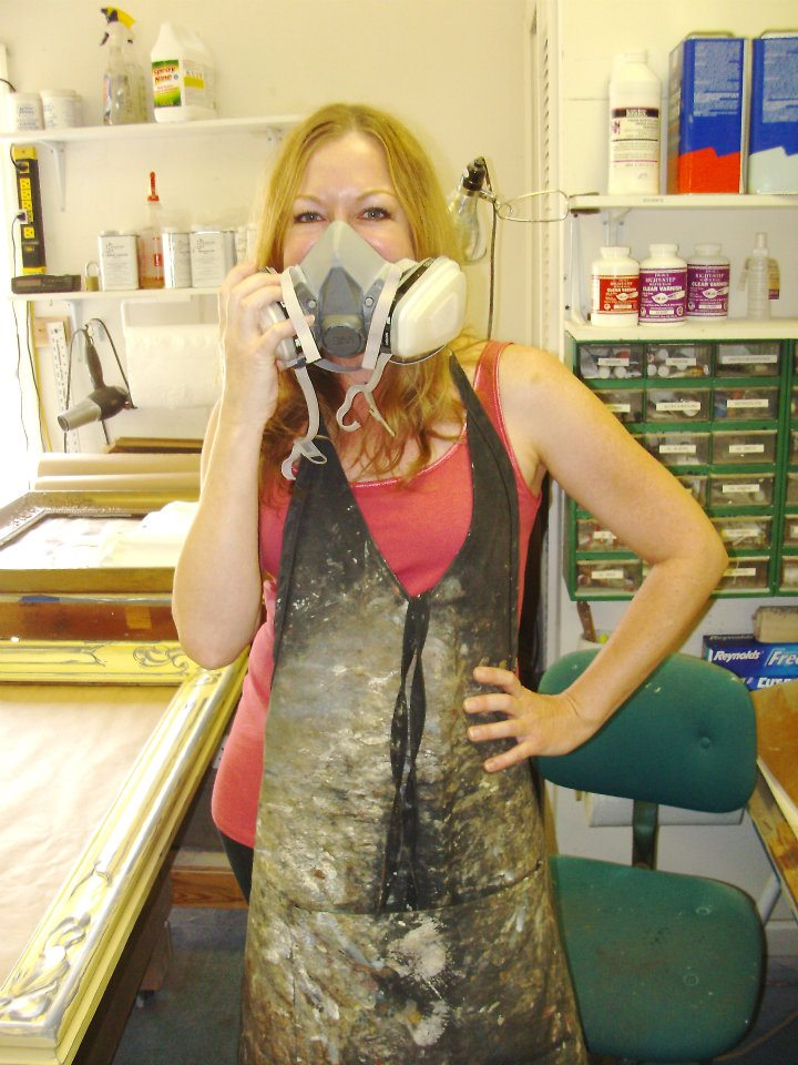 Kate displaying some of the tools of her trade: a respirator and a well-worn smock.